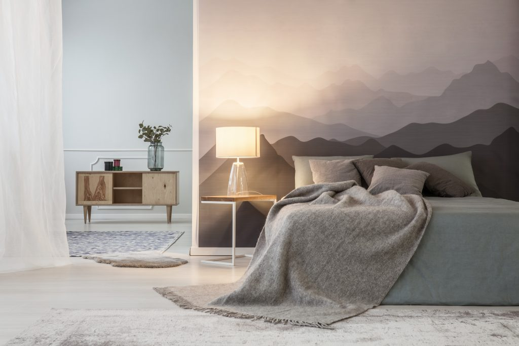 Illuminated mountain lover's open space bedroom interior with a wooden cabinet and a gray cozy bed against a landscape wallpaper