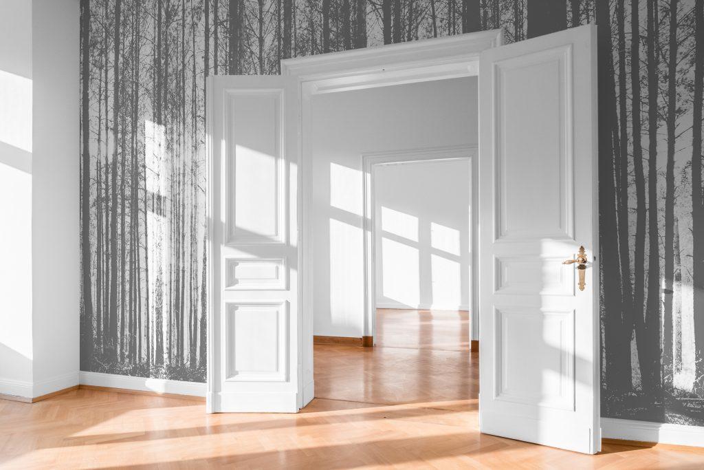 open room door in bright flat with photo wallpaper